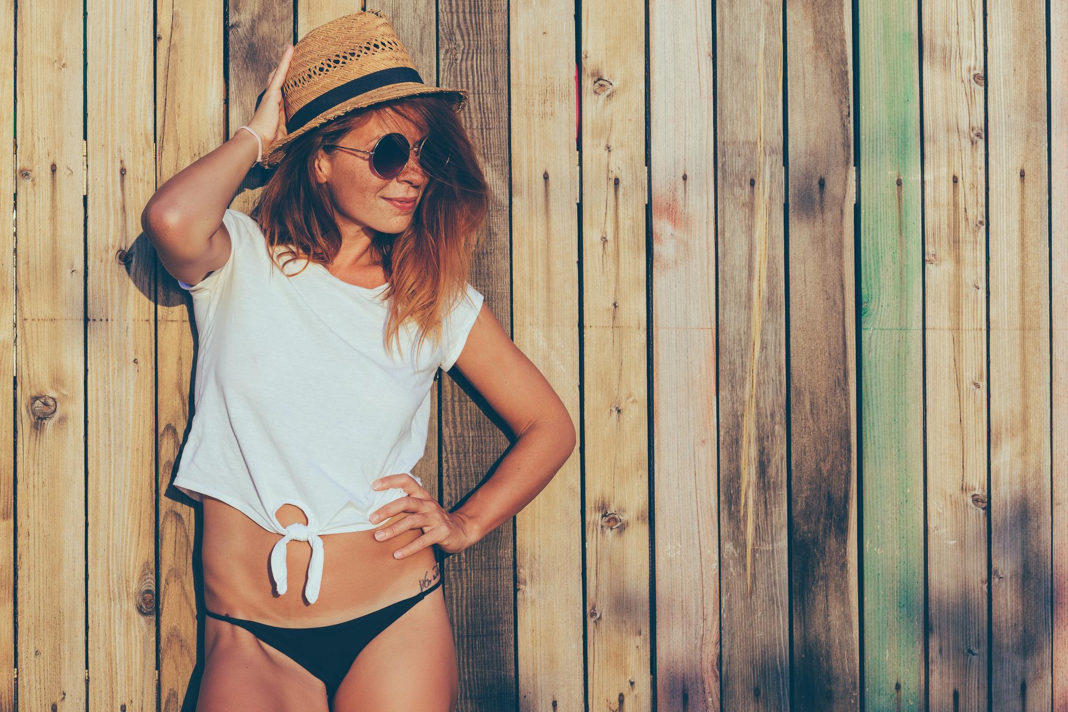Mulher usando óculos de sol, chapéu e biquíni
