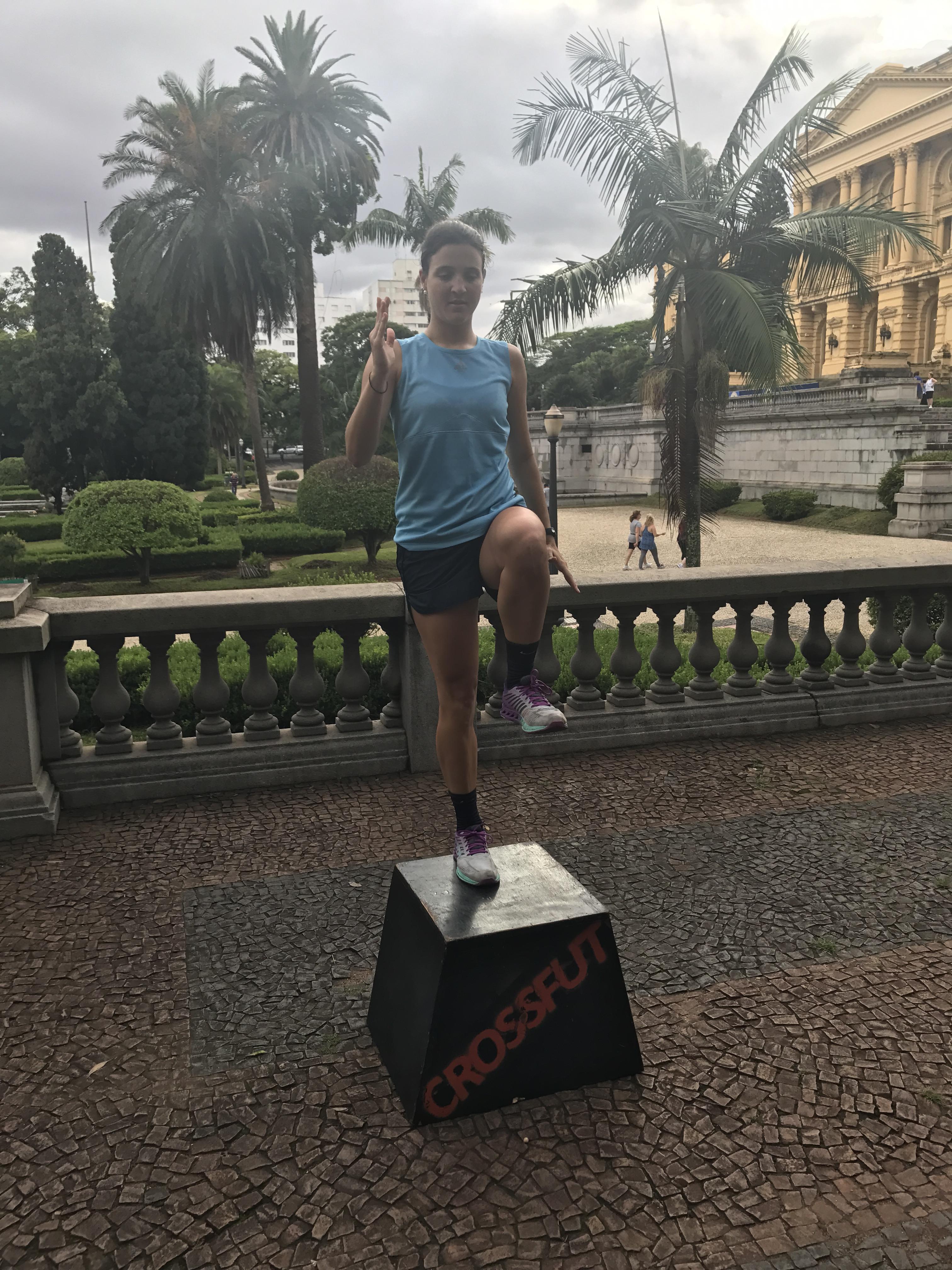Mulher fazendo subindo na caixa com elavação de joelho no treino de Crossfut
