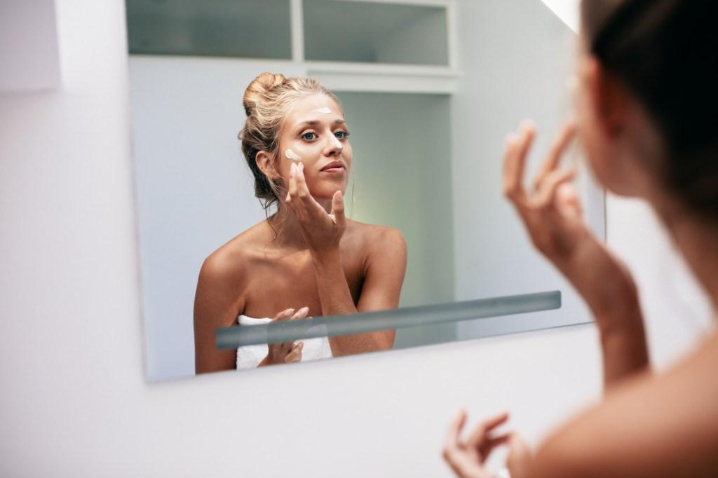 Mulher no espelho passando creme no rosto