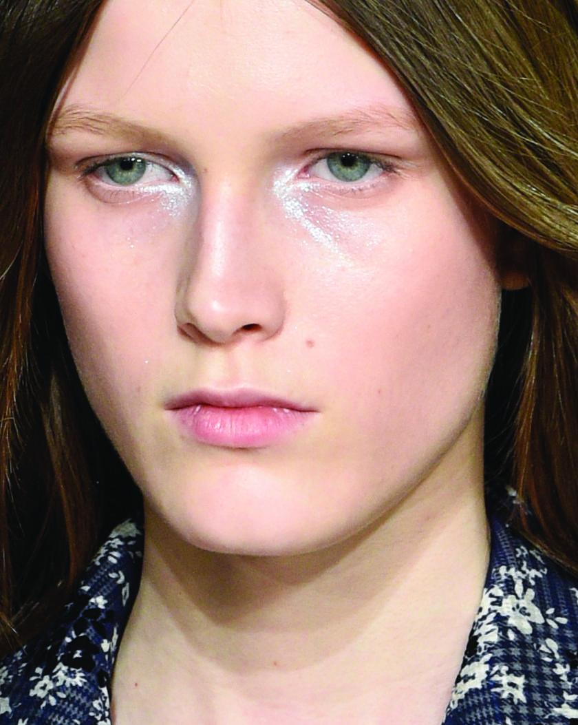 Close de maquiagem de modelo com iluminador nos olhos