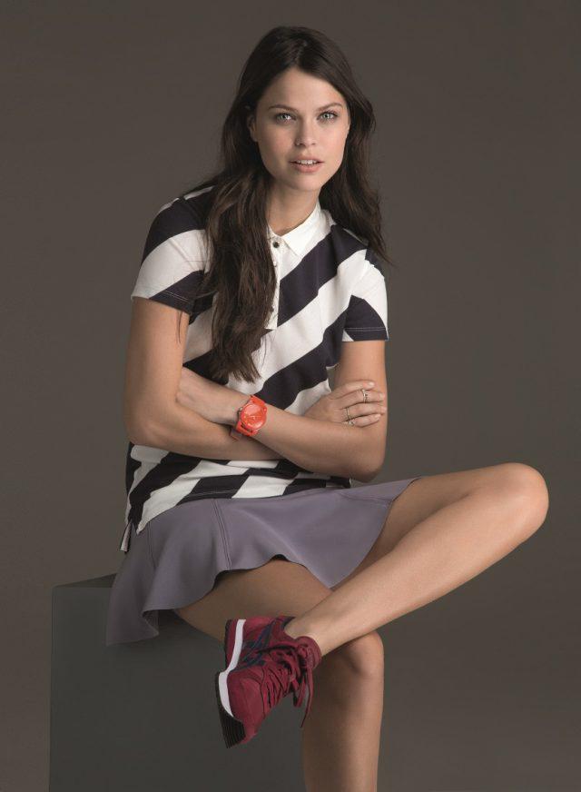 Modelo sentada com camiseta polo, saia e tênis