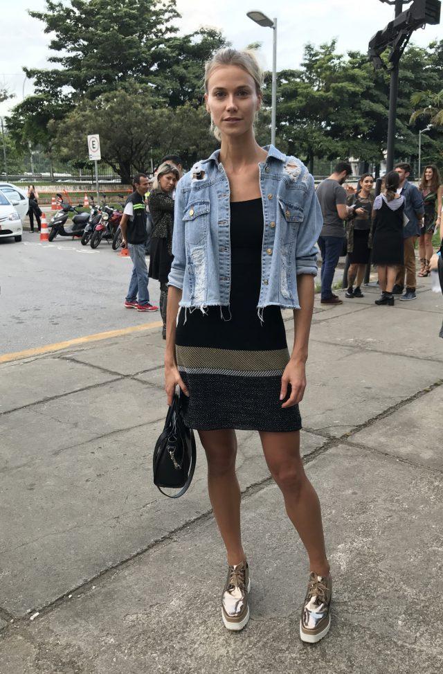 Modelo Renata Kuerten no SPFW com vestido, jaqueta jeans e tênis