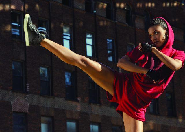 Mulher dando um chute com conjunto de plush vermelho