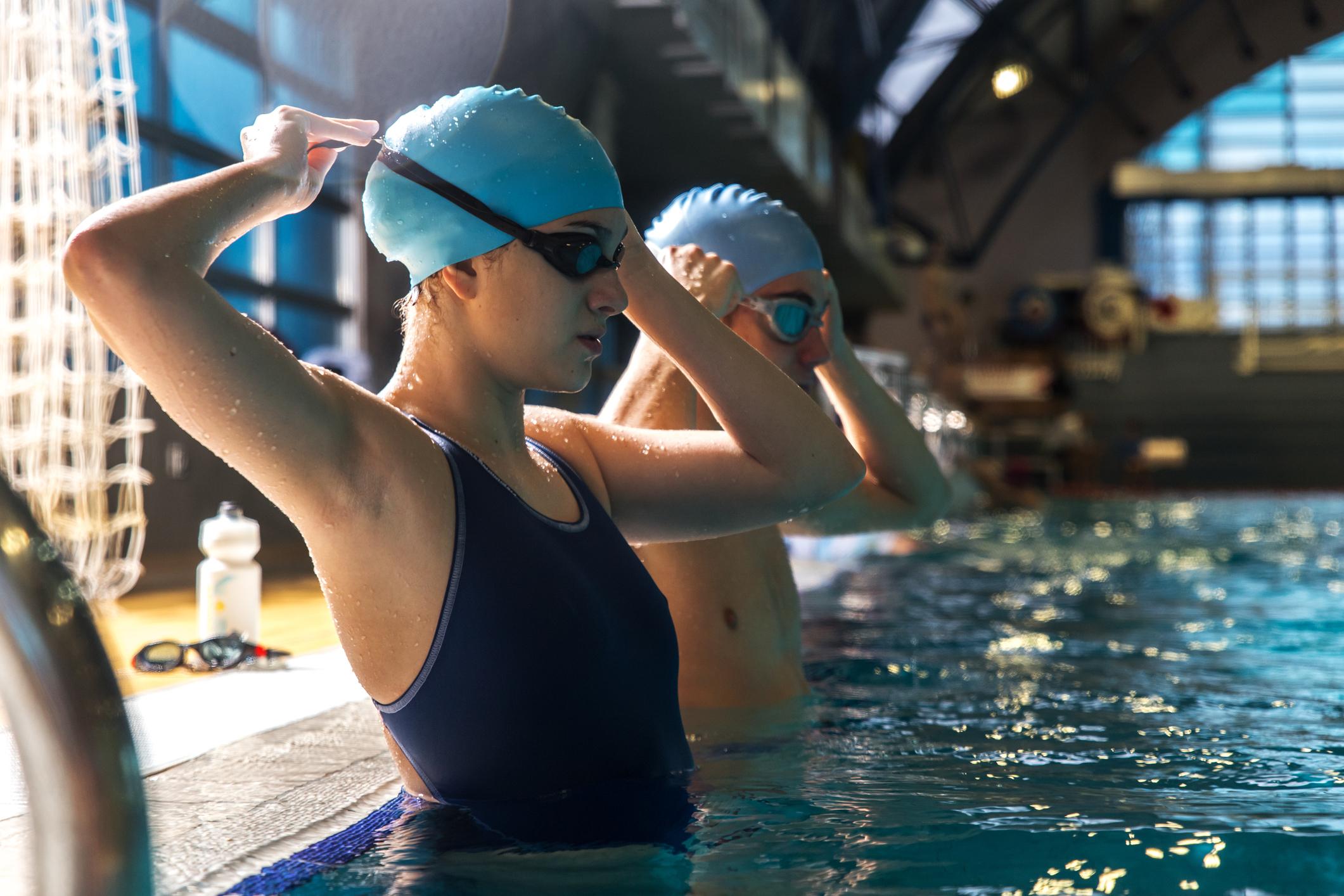 Casal dentro de uma piscina com touca e óculos de natação