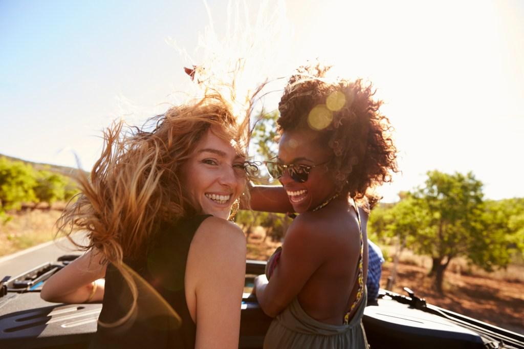 Duas amigas andando de carro conversível com o cabelo ao vento