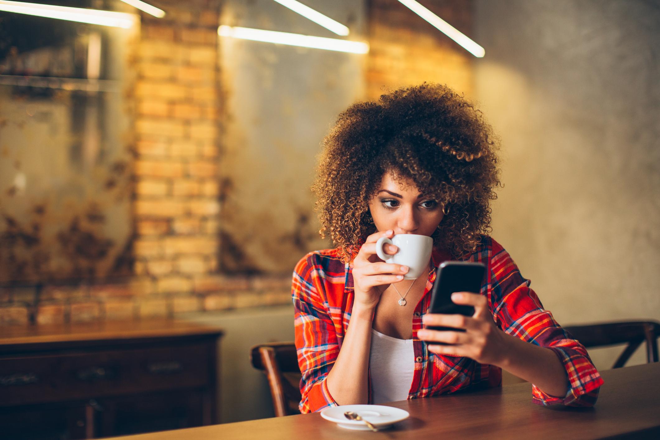 Mulher negra tomando café e olhando o celular