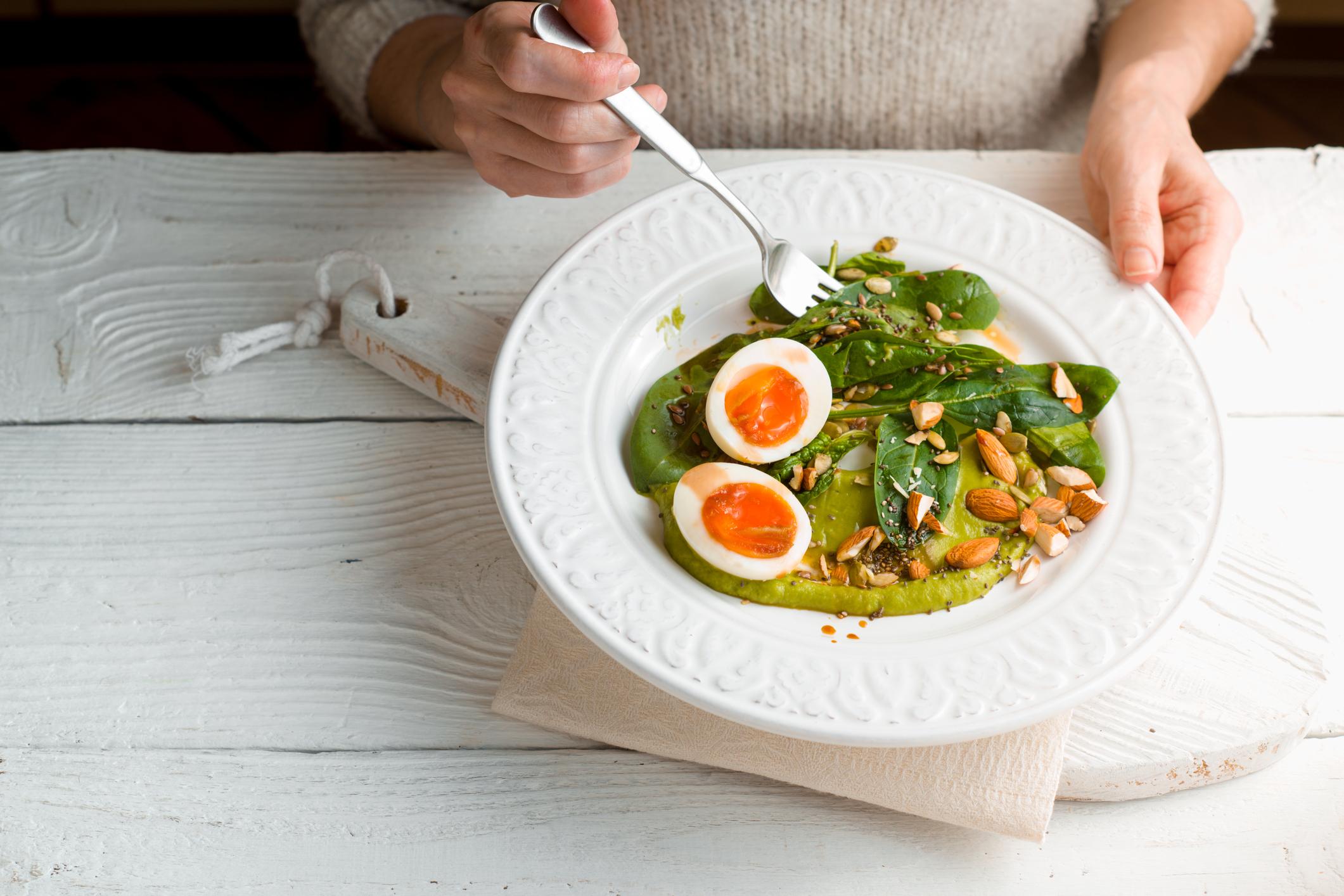 Mulher comendo salada com ovos