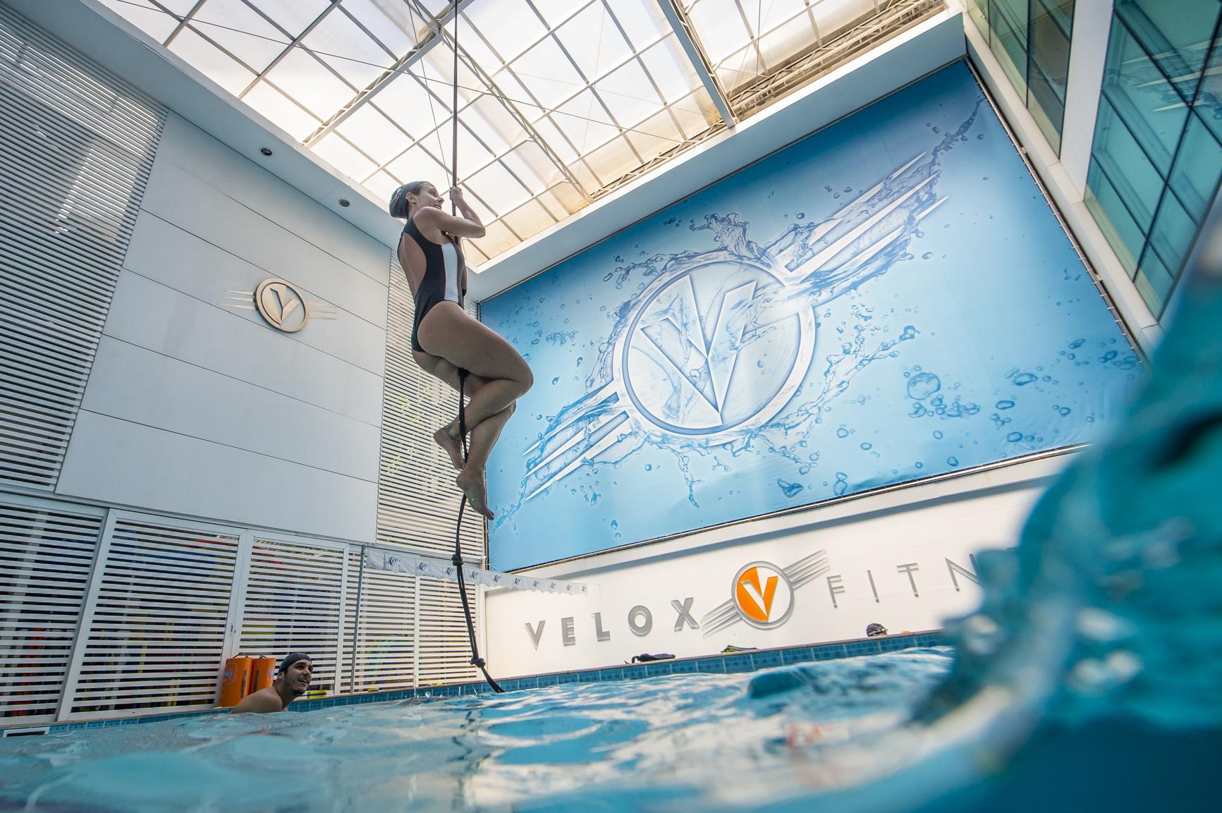 Mulher escalando corda na piscina na aula de cross swim
