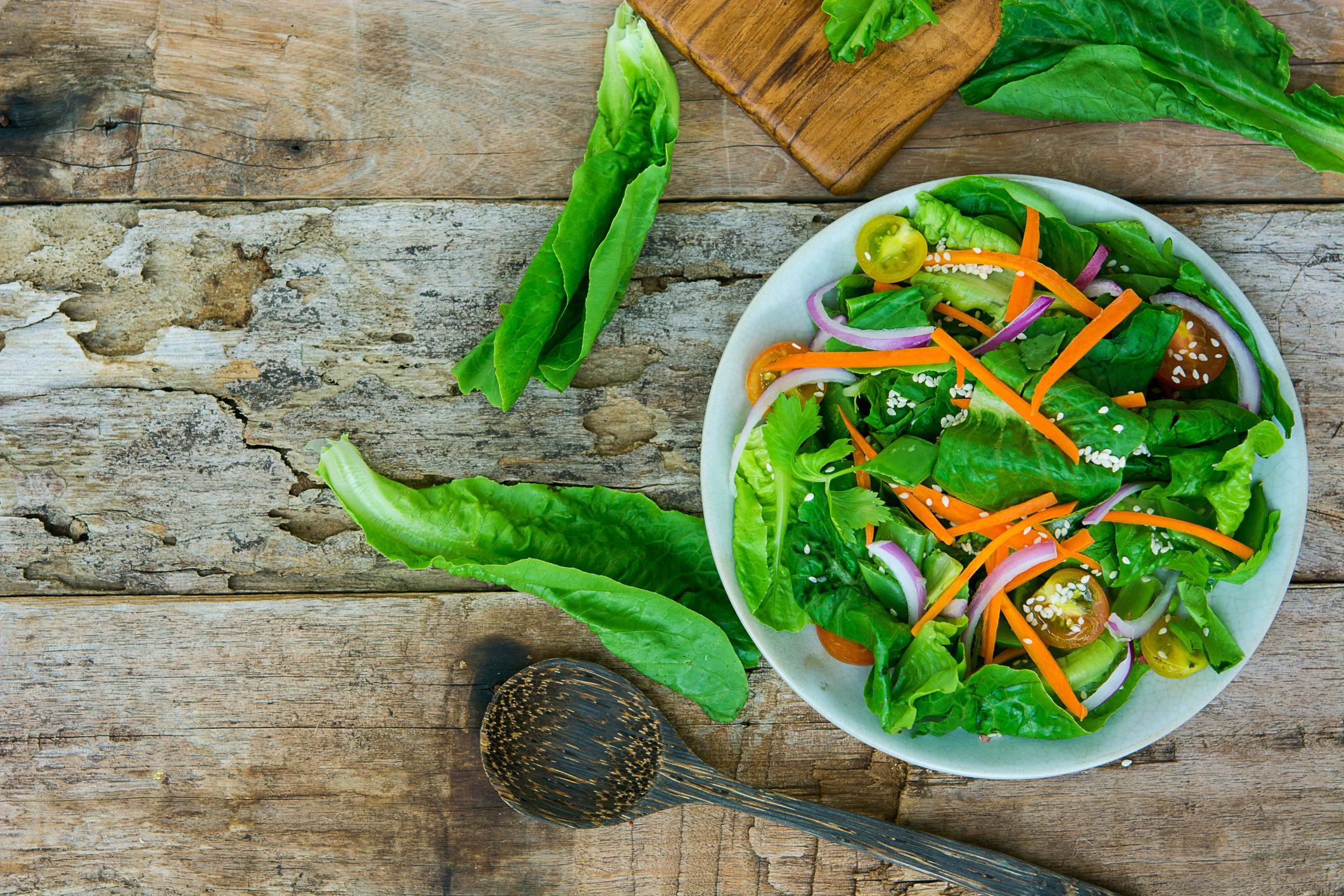 Salada vegetariana com verdes, cenoura e outros vegetais em um bowl sobre uma mesa rústica