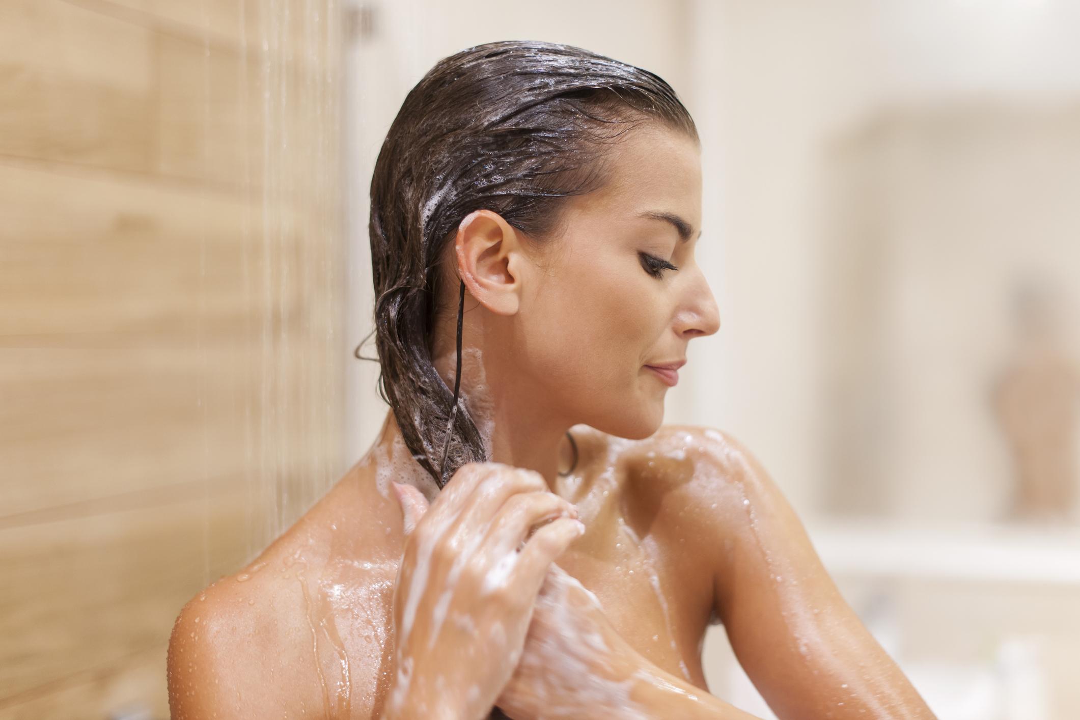 Mulher lavando o cabelo no banho