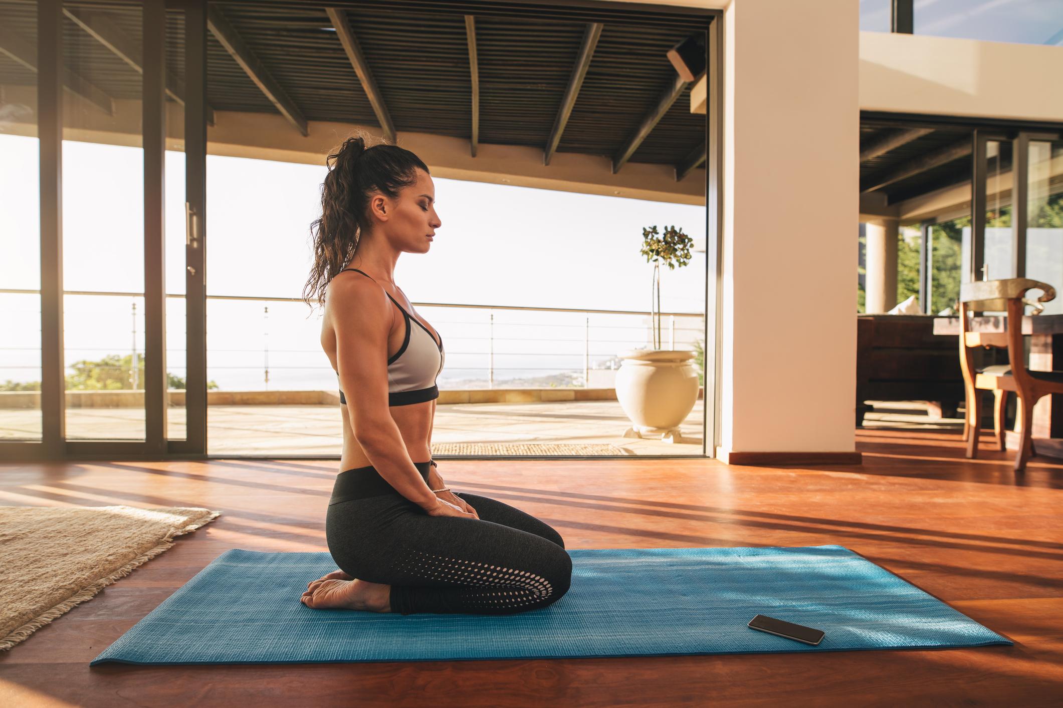 Mulher fotografada de perfil com roupa de ginástica praticando ioga em casa