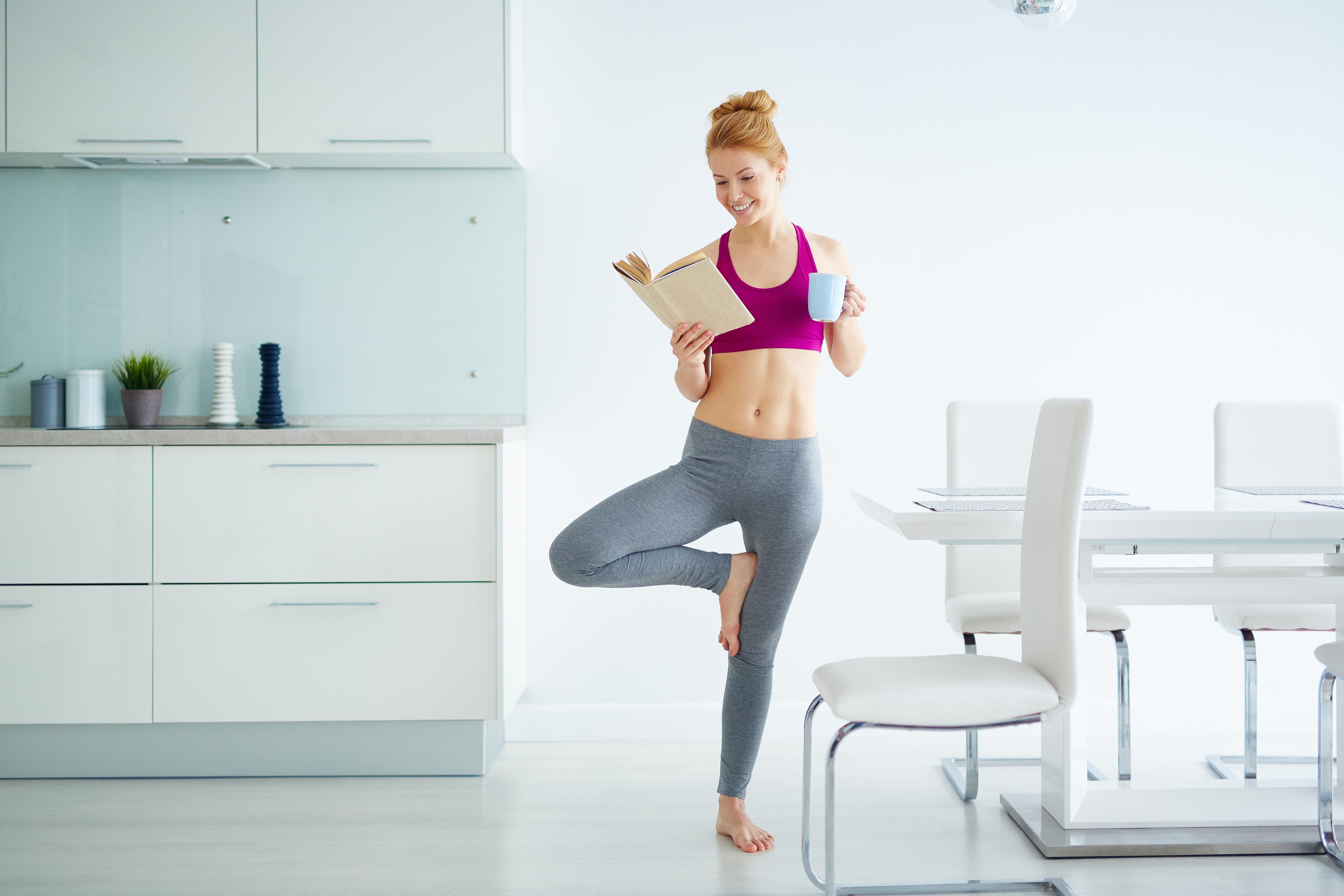 Mulher com roupas de ginástica lendo livro