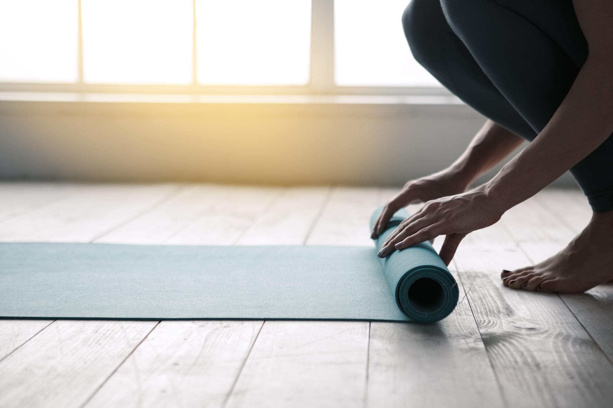 Mulher desenrolando mat de ioga