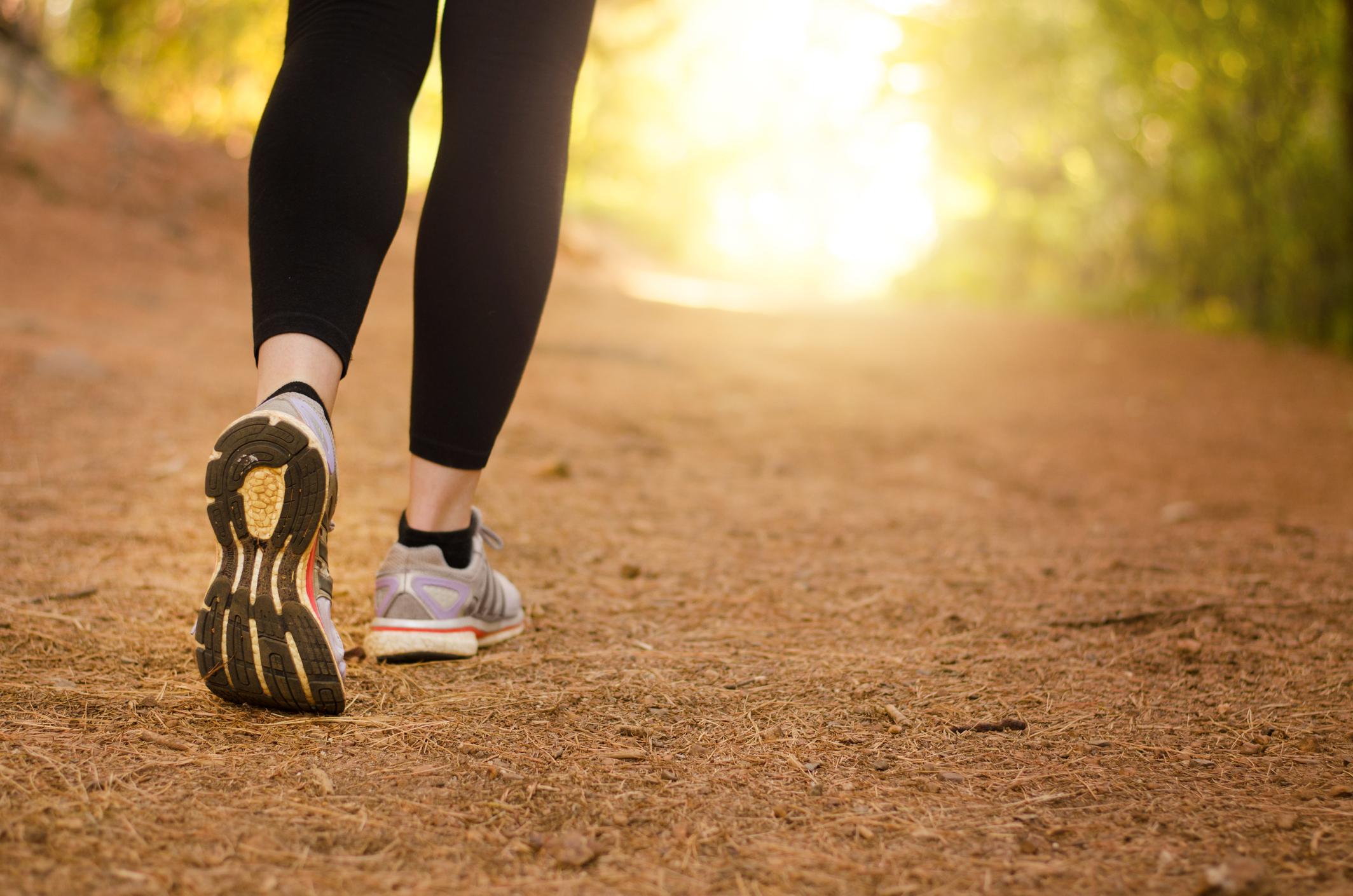 Mulher caminhando no parque com roupa fitness e tênis de corrida