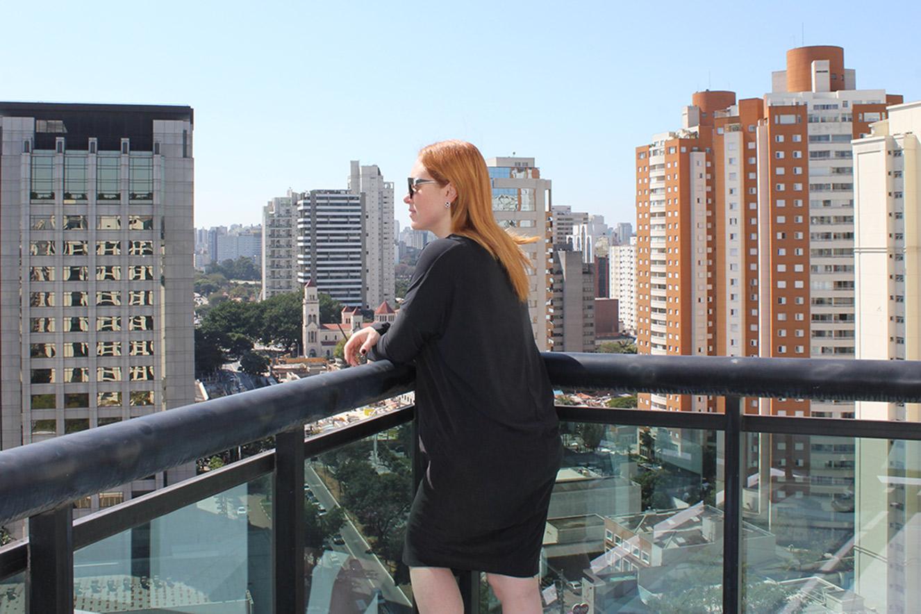 Cacá Filippini em varanda com vista para a cidade