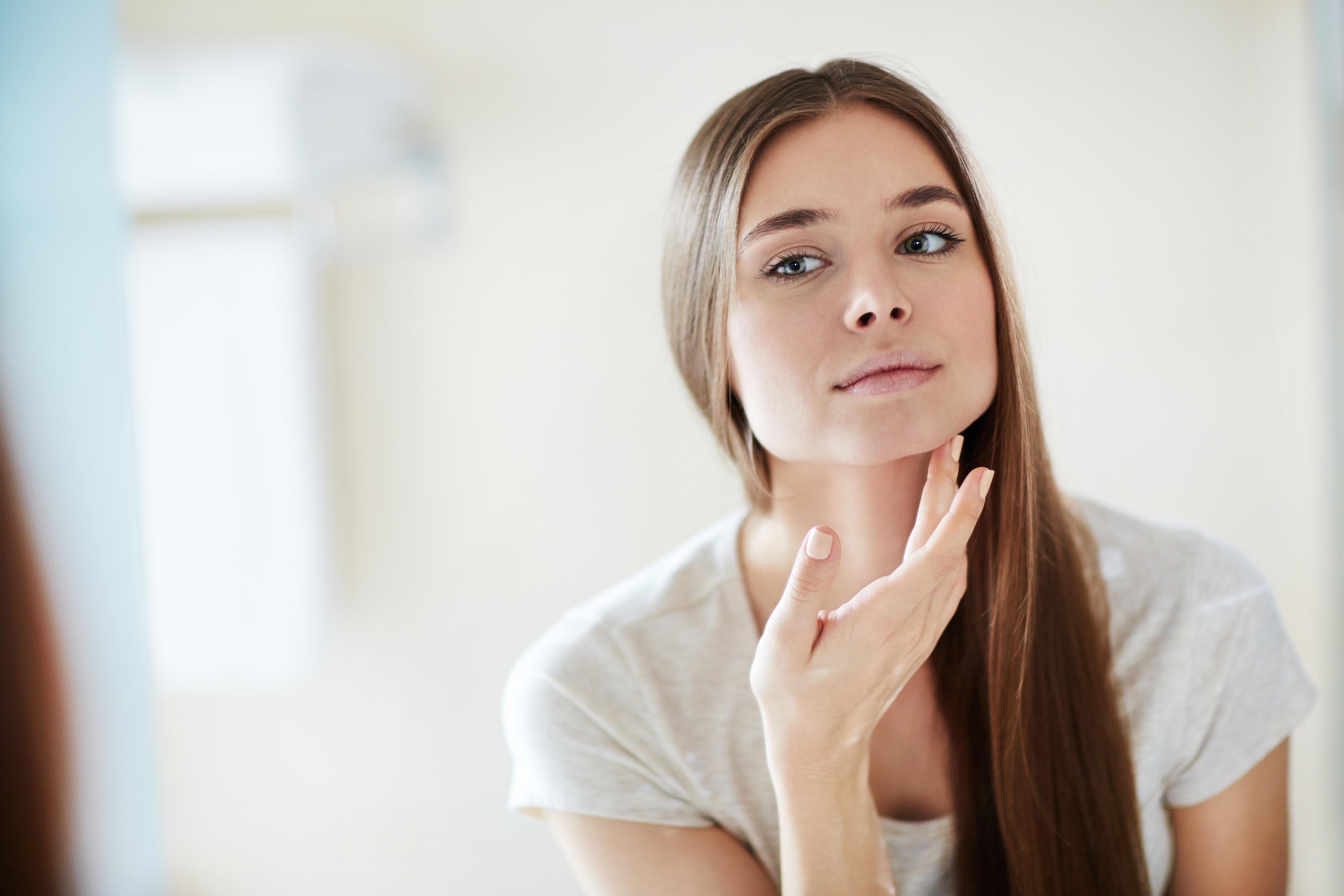 Mulher jovem olhando a pele do rosto