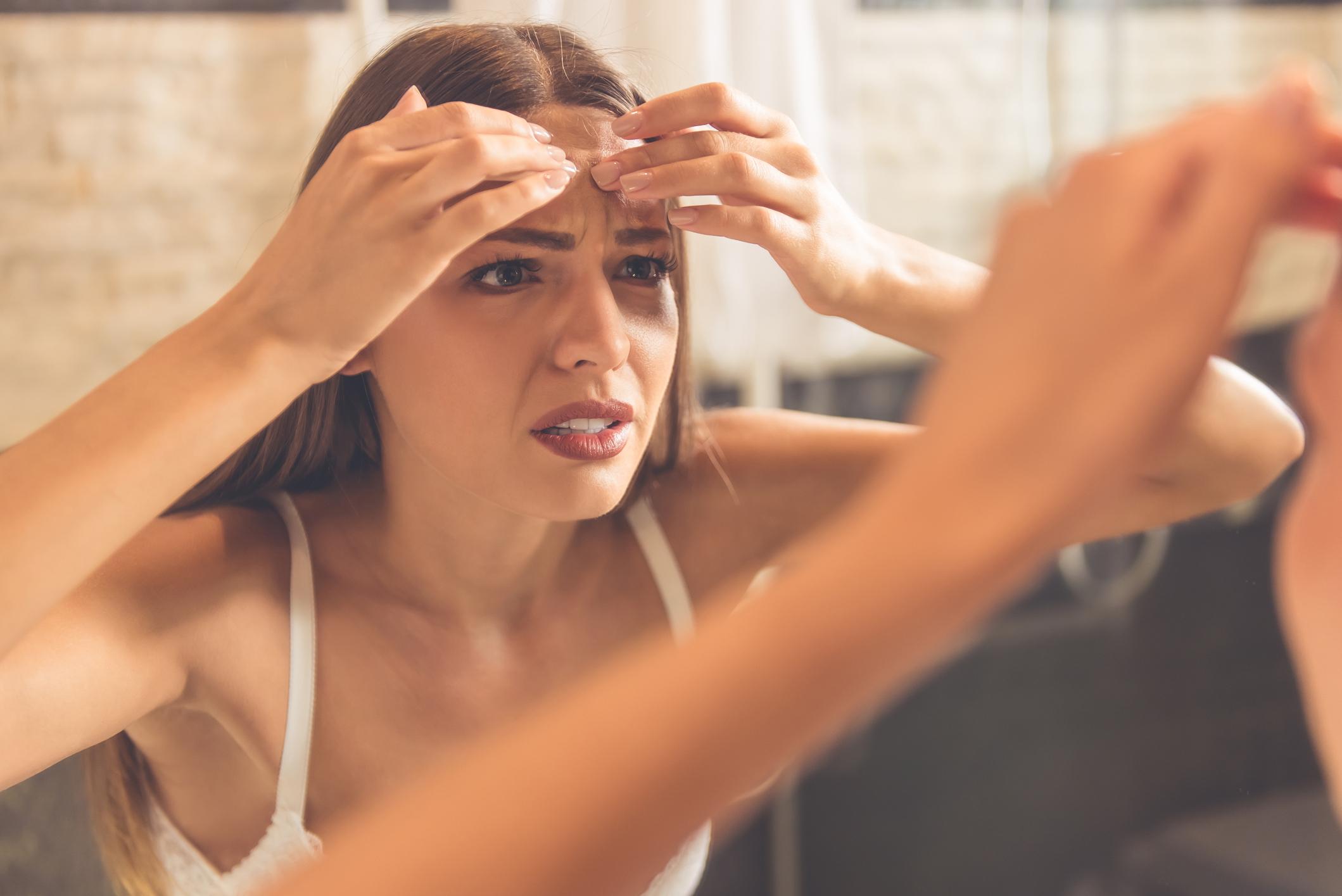 Mulher estressada olhando a pele do rosto no espelho