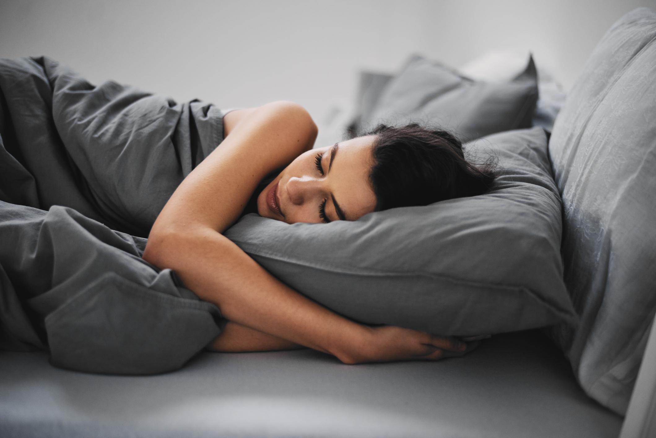 Mulher jovem dormindo em cama