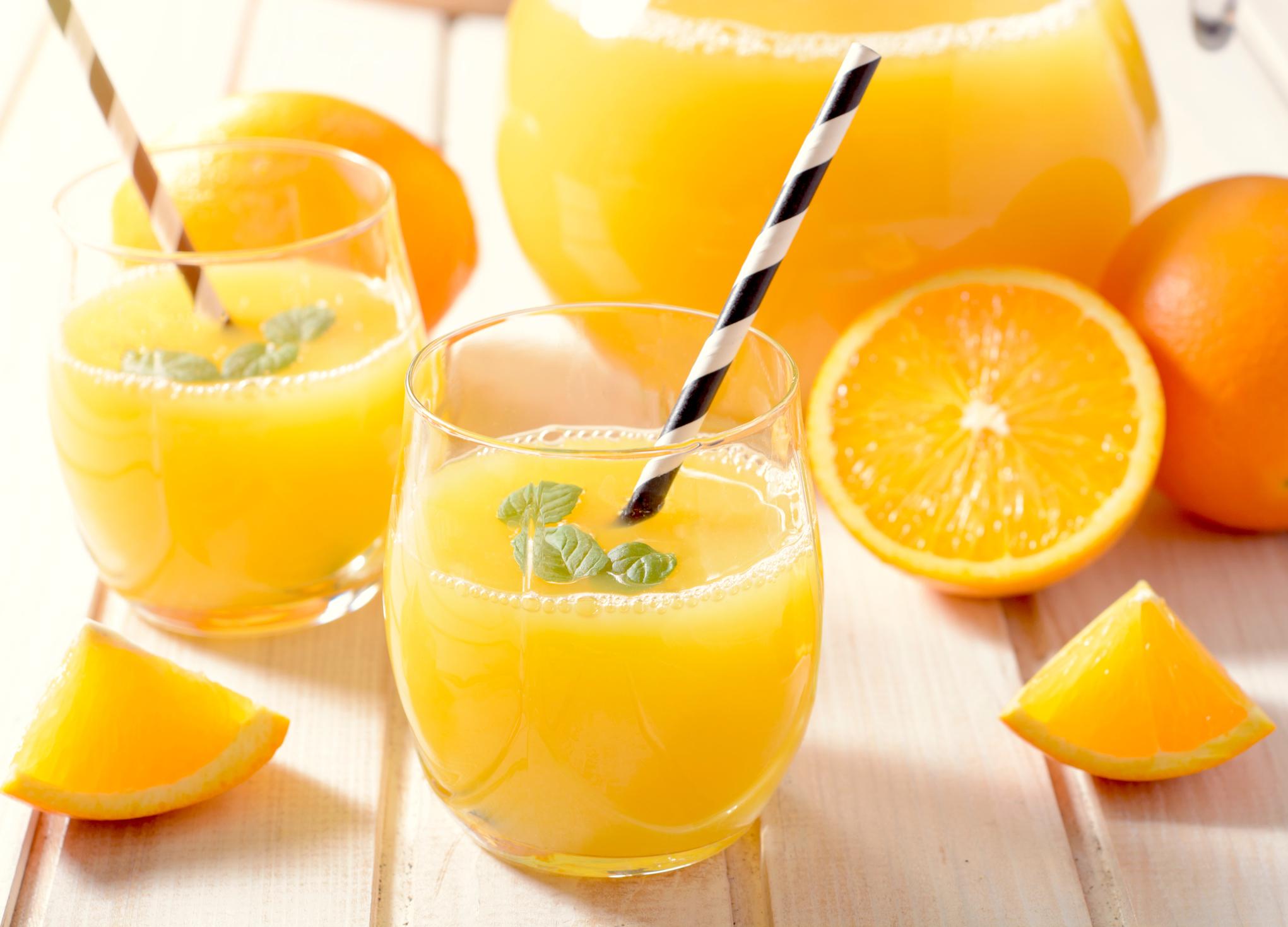 Jarra de suco de laranja com várias frutas cortadas e dois copos com canudo