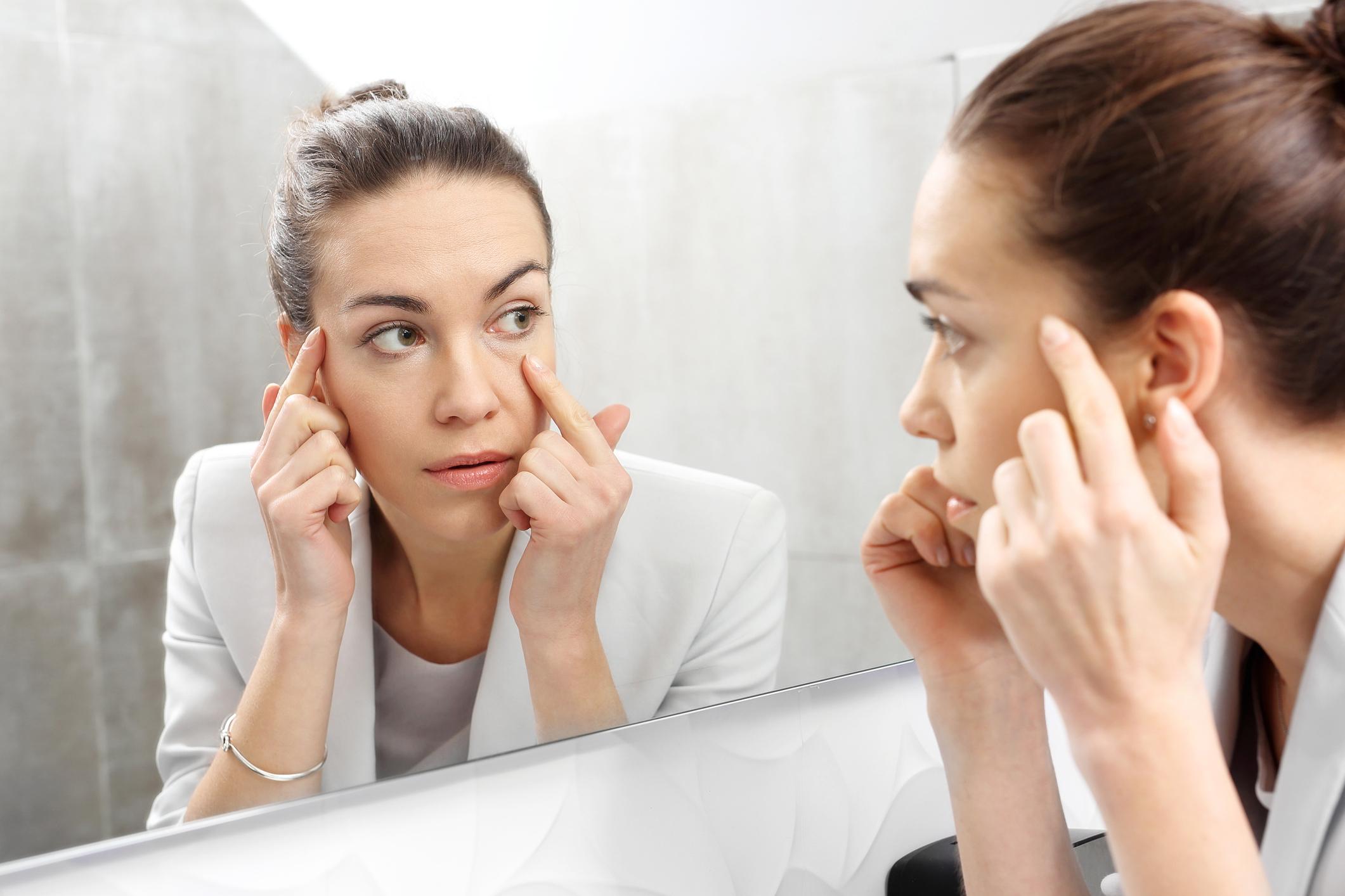 mulher olhando olheiras no espelho