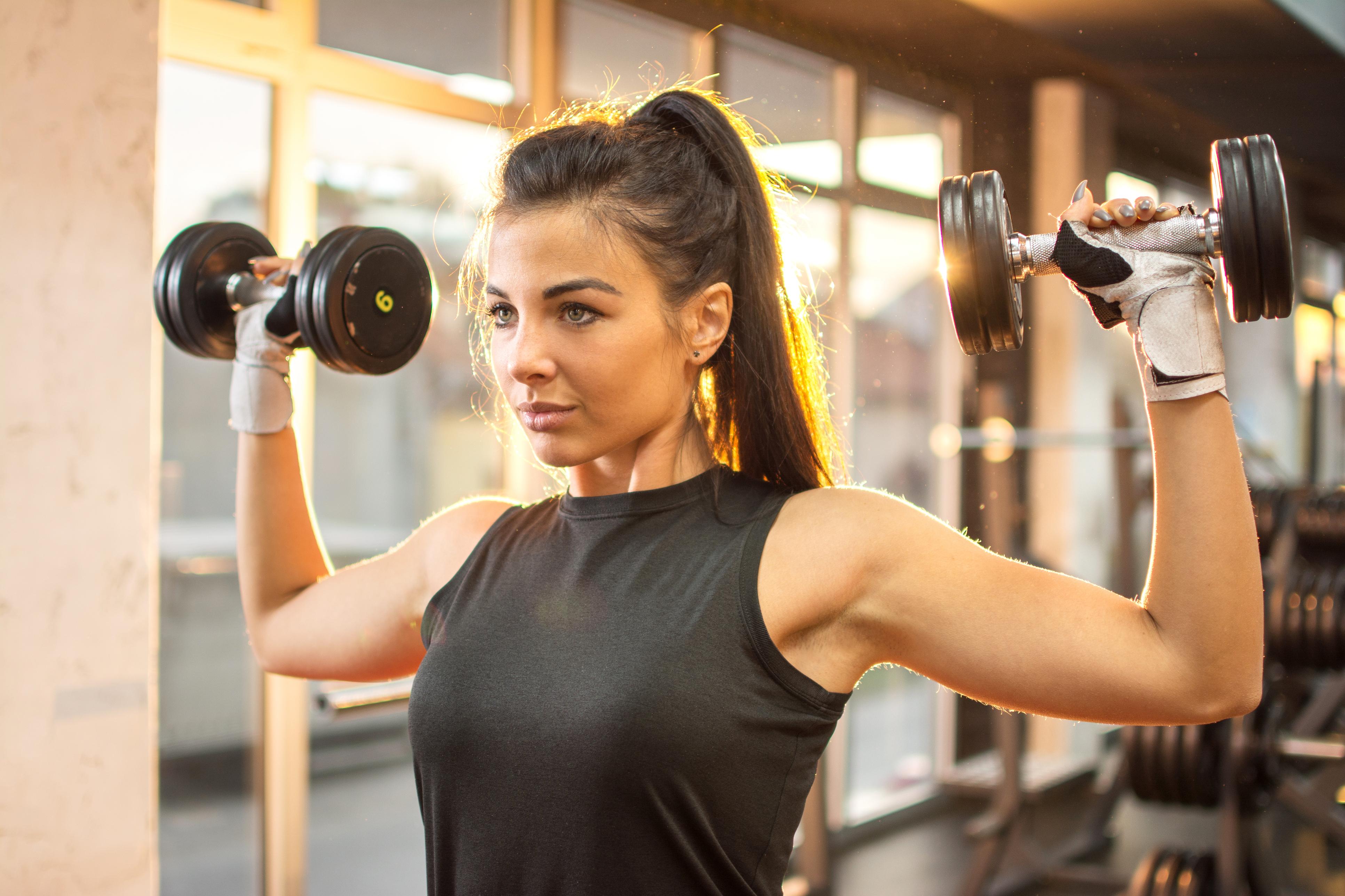Mulher treinando musculação com halteres na academia