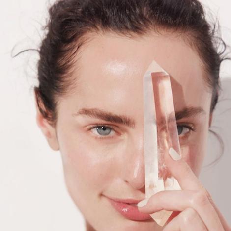 mulher com pele limpa segurando um cristal