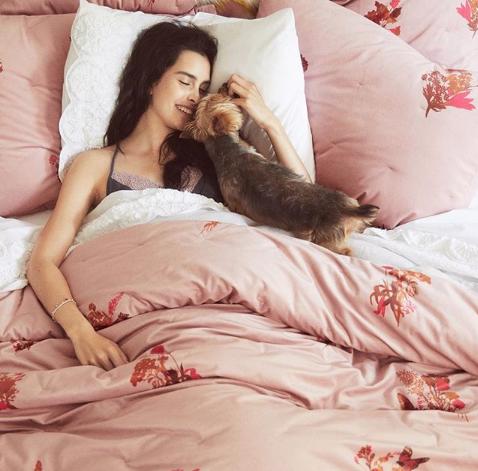 mulher dormindo em cama confortável com seu cachorrinho