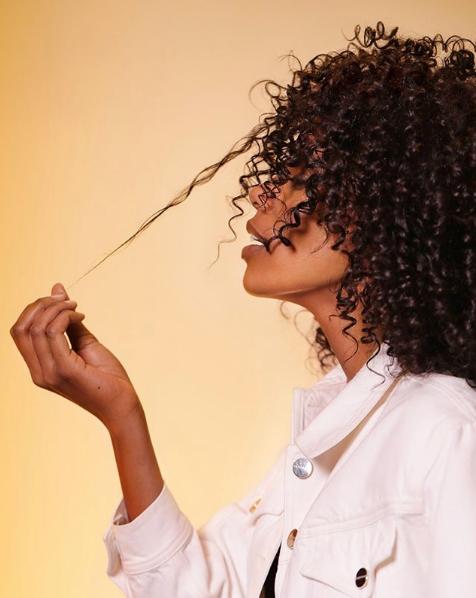 mulher puxando os cachos do cabelo