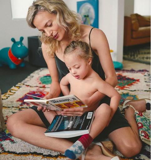 Mulher lendo para a filhinha que está sentada no colo dela