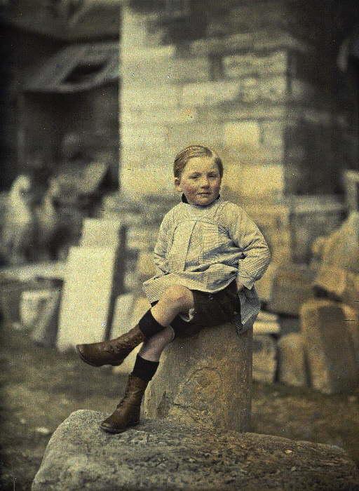 Menino sentado em uma pedra, provavelmente um depósito da catedral, na França, em 1º de abril de 1917. (foto: worldwaronecolorphotos.com)