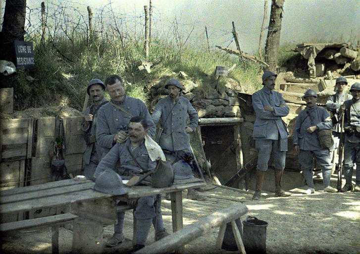 """Corte de cabelo dos soldados. A placa """"Ligne de résistance"""" na esquerda significa Linha de Resistência. Sem data. (Foto: worldwaronecolorphotos.com)"""