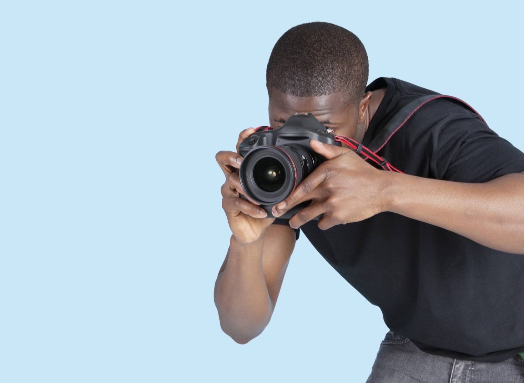 Young man taking photo through digital camera over blue background
