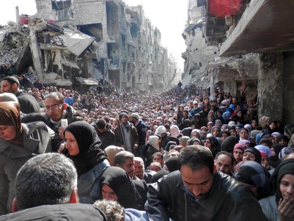 Centenas de pessoas esperam a chegada da ajuda humanitária da ONU para receber comida em Damasco: Guerra civil na Síria já matou cerca de meio milhão de pessoas (foto: Getty Images)