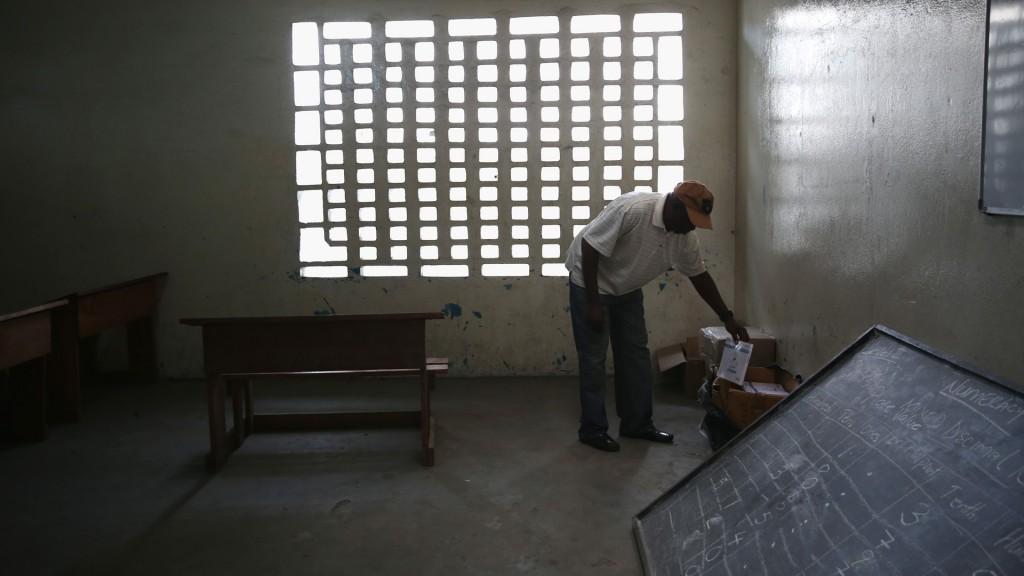 Um funcionário do serviço de saúde na Libéria pega um livro em uma sala de aula anteriormente usada como centro de atendimento para pacientes com ebola. Foto: Getty Images.