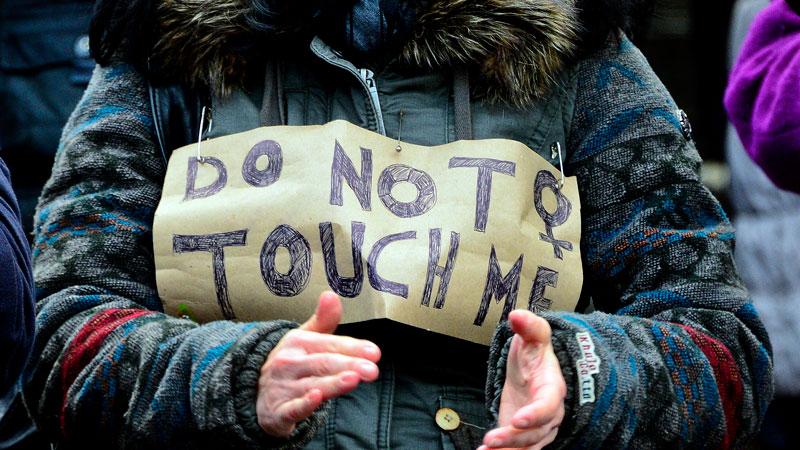 """Mulher carrega placa com os dizeres """"Não toque em mim"""" em protesto contra ataques no Ano-Novo (Getty Images)"""