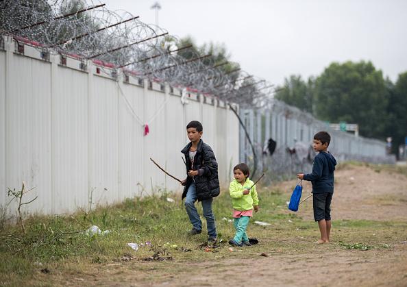 Crianças refugiadas em frente à barreira na cidade de Horgos, na fronteira entre a Sérvia e a Hungria, em julho de  2016  (Matt Cardy/Getty Images)