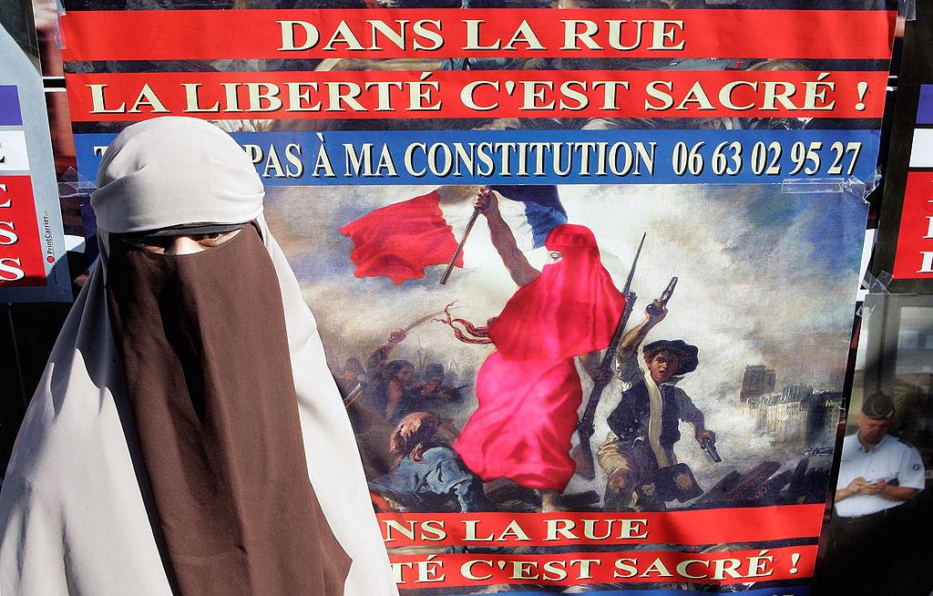 """Mulher protesta em Paris, na França, contra a proibição do uso do niqab (tipo de véu islâmico que deixa visíveis apenas os olhos), em 2011. O cartaz diz """"na rua a liberdade é sagrada"""""""