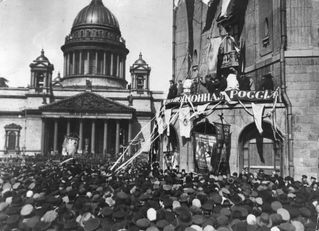 Foto em preto e branco de uma multidão reunida na frete de uma igreja ouvindo um discurso de pessoas na parte de cima de um edifício