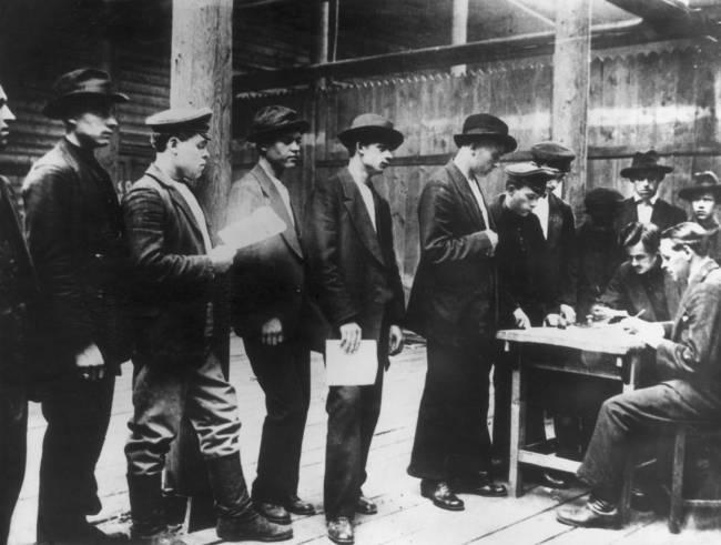 Foto em preto e branco de homens em fila, com papéis na mão, esperando a sua vez para serem atendidos por uma dupla de homens bem vestidos sentados em uma mesa