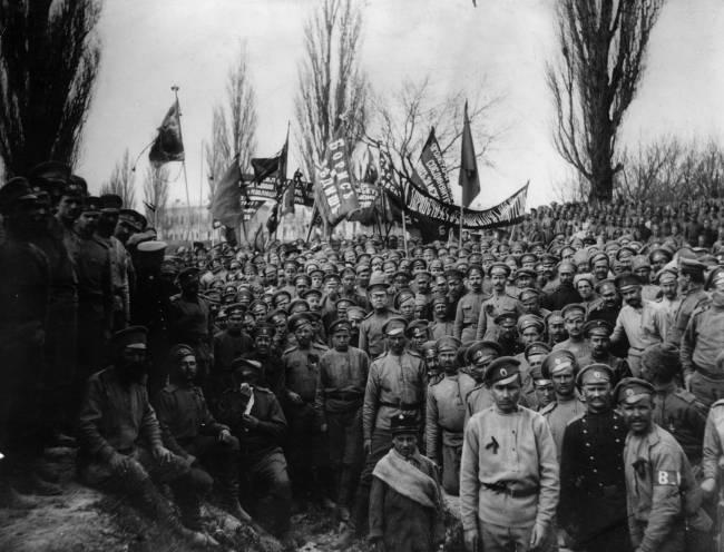 Foto preta e branca dos membros do Exército Russo posando com bandeiras com dizeres republicanos