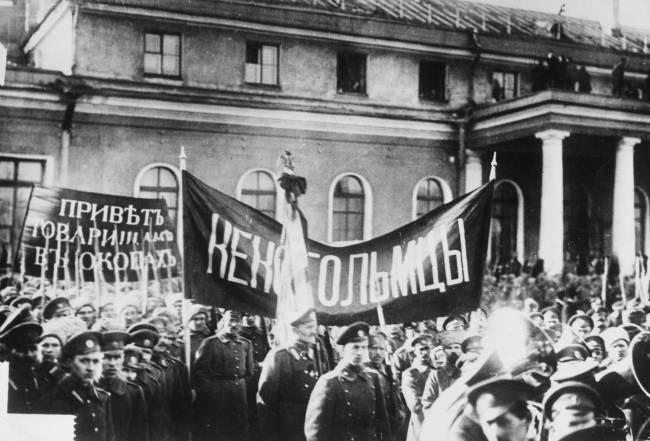 Foto preta e branca de soldados com bandeiras com dizeres em russo, em frente a um prédio de arquitetura clássica