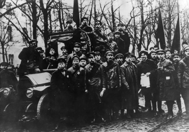 Foto preta e branca dos membros do Exército Vermelho posando em frente e em cima de um carro