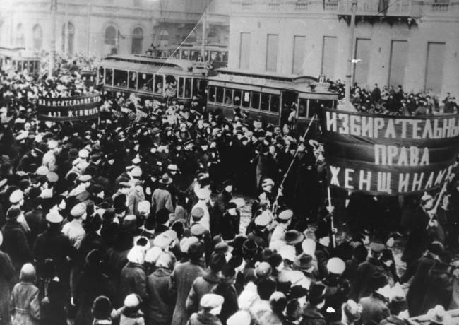 Foto preta e branca de uma massa de mulheres protestando e levando bandeiras com dizeres em russo