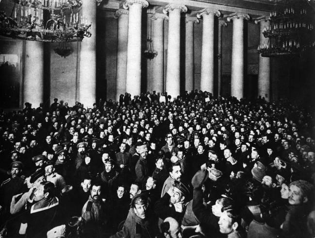 Foto preta e branca de uma sala, com colunas e arquitetura clássica, cheia de soldados ouvindo