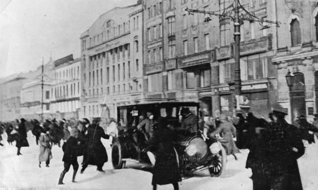 Foto em preto e branco de pessoas correndo de tiros em uma avenida com vários prédios e um carro