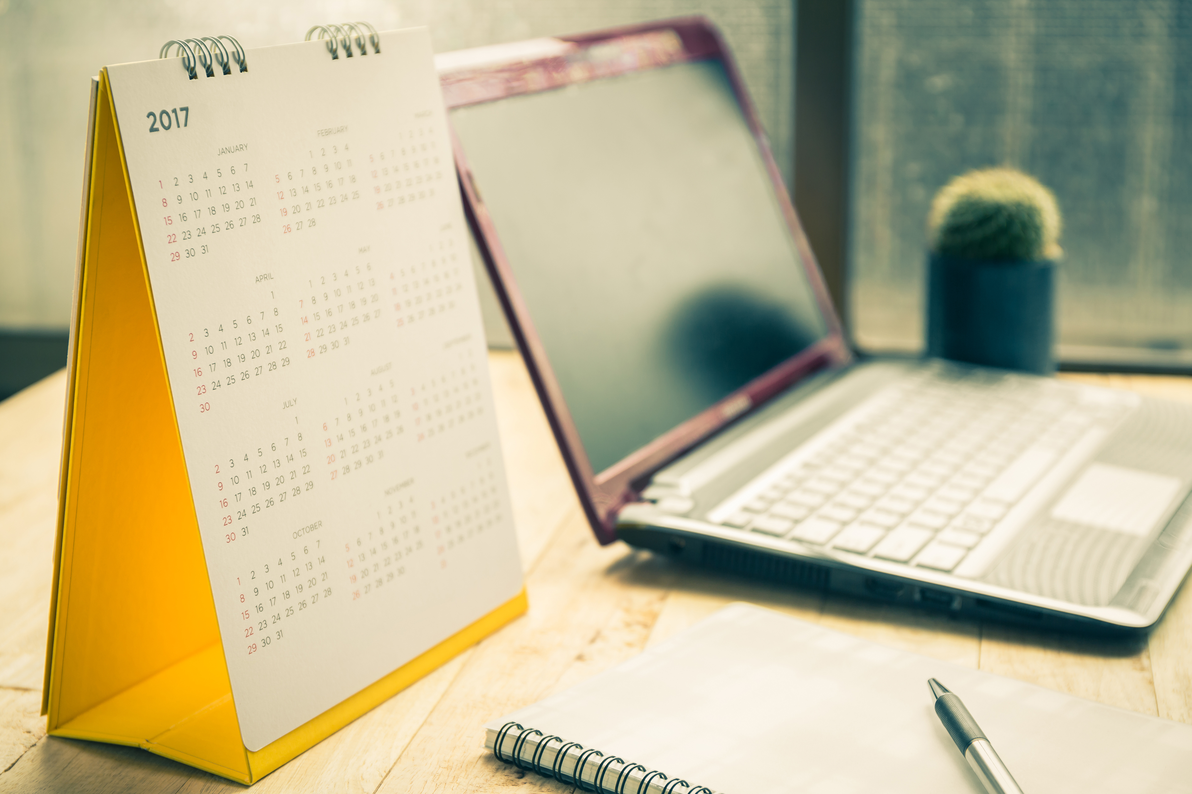 Uma mesa com um laptop, um calendário de 2017 e um caderno com uma caneta em cima