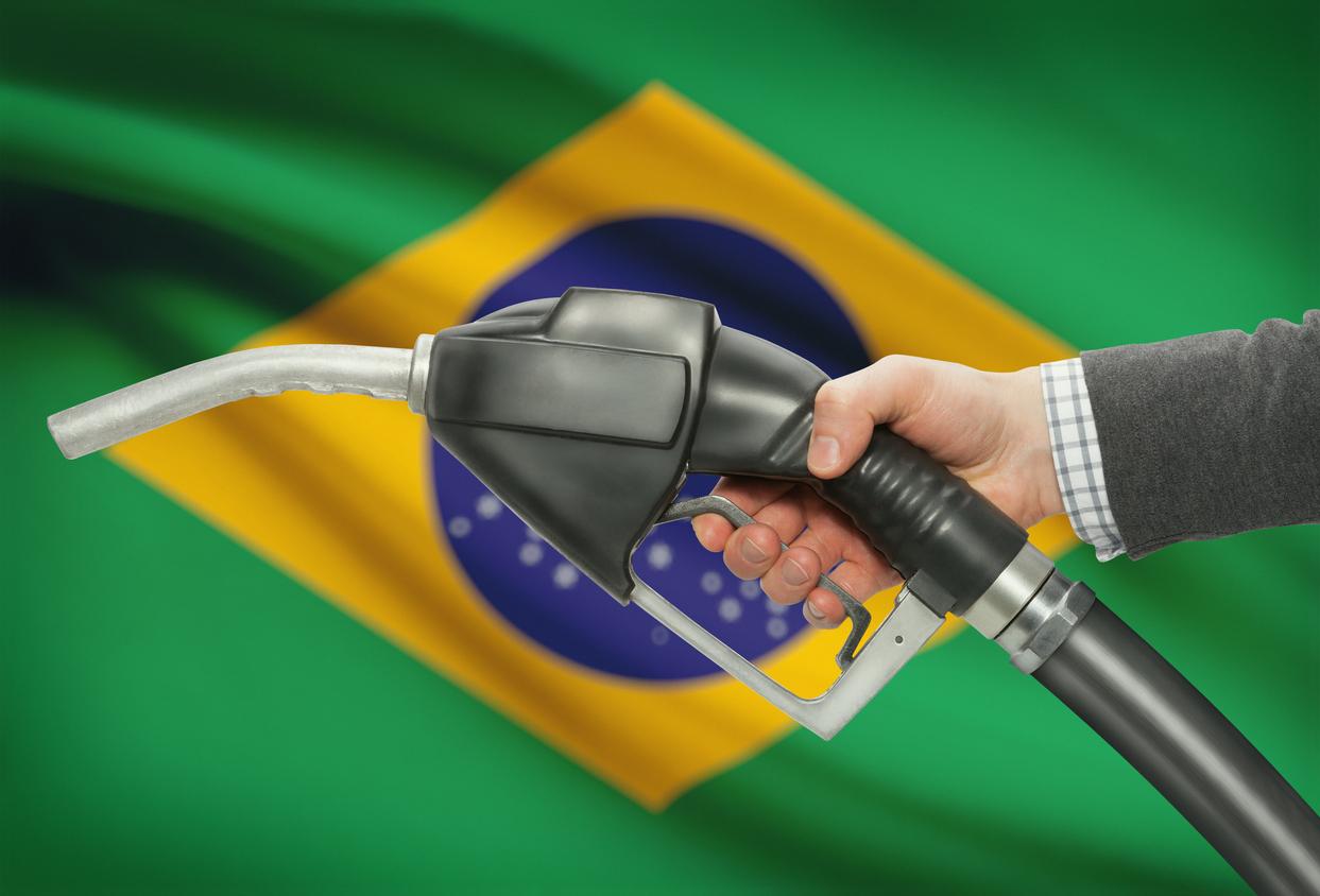 Bomba de gasolina com bandeira do Brasil ao fundo